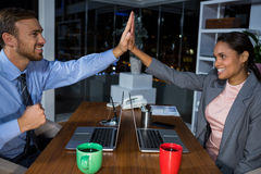 Business executives giving high fives while working in office Royalty Free Stock Photos