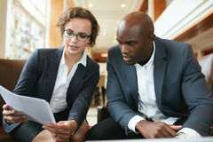 Business executives going through papers in lobby. Two business partners sitting together and discussing contract documents. Business executives going through royalty free stock images