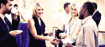 Business executives interacting with each other while having coffee. At conference center royalty free stock photo