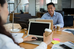 Business executives interacting with each other while using laptop at desk Royalty Free Stock Photography