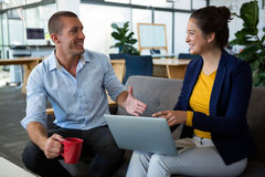 Business executives interacting with each other while using laptop Stock Image