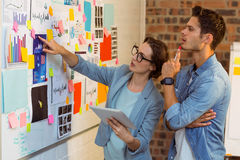Business executives looking at sticky notes and graph on white board Royalty Free Stock Images