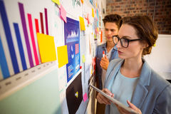 Business executives looking at sticky notes on whiteboard Royalty Free Stock Images