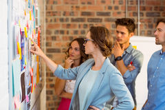 Business executives looking at sticky notes on whiteboard Stock Photo