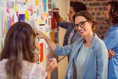 Business executives looking at sticky notes on whiteboard. In office stock images