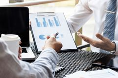 Business Executives meeting with data of sales performance at a modern outdoor workplace.  stock photos