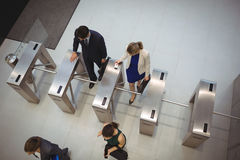 Business executives passing through turnstile gate. Top view of business executives passing through turnstile gate Royalty Free Stock Photo