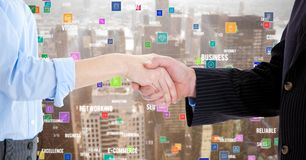 Business executives shaking hands against cityscape in background Royalty Free Stock Image