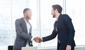 Business executives shaking hands, making successful deal. In office royalty free stock photography