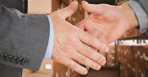 Business executives shaking hands in warehouse. Digital composite of Business executives shaking hands in warehouse royalty free stock images