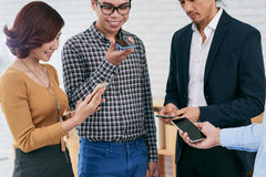 Business executives with smartphones. Group of Vietnamerse business people using smartphones stock photo