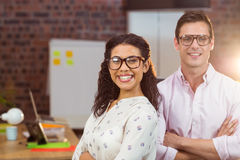 Business executives standing with arms crossed in office Stock Photo