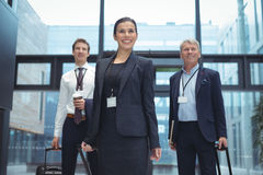 Business executives with trolley bag standing. In the office Stock Images