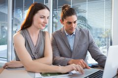 Business executives using laptop at desk. In office Royalty Free Stock Images