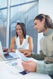 Business executives using laptop at desk. In office Royalty Free Stock Photos