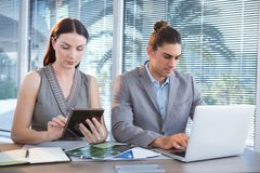 Business executives using laptop and digital tablet at desk. In office Stock Images