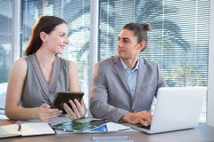 Business executives using laptop and digital tablet at desk. In office Royalty Free Stock Images