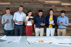 Business executives using mobile phone and digital tablet. In office Royalty Free Stock Photo