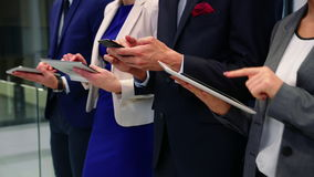 Business executives using mobile phone and digital tablet in office stock video