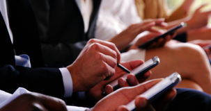 Business executives using mobile phone. Mid section of business executives using mobile phone at conference center stock footage