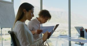 Business executives working in conference room of modern office 4k. Side view of young diverse business executives working in conference room of modern office stock video footage
