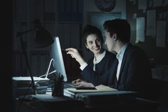 Business executives working in the office. Business executives working together in the office, they are discussing a project and connecting with a computer royalty free stock image