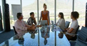 Business executives working at table in conference room of modern office 4k. Front view of diverse business executives working at table in conference room of stock footage