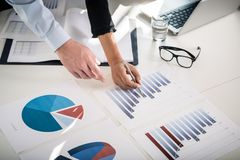 Business experts analyzing statistical bar and pie charts. Business experts analyzing statistical information from vertical bar and pie charts printed in the Royalty Free Stock Photo
