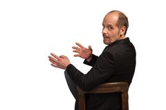 Business explanation. A well dressed Businessman is sitting on a chair to explain something on a white background royalty free stock image