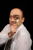 Business eye. Businessman in business clothing looking through magnifying glass; his eye is enlarged Royalty Free Stock Photography