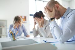 Stressed business team with papers at office stock photography