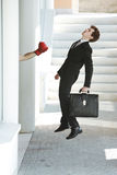 Business failure. Young businessman gets knocked out by a punch, business failure concept Stock Image