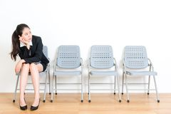 Business female model sitting on wood floor chair stock image