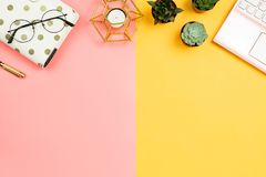 Business feminine mockup with smartphone pink laptop, succulent flowers. Glasses, pen, planner and candle, pastel pink and yellow background. Copyspace royalty free stock photo