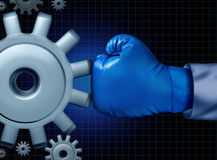 Business Fight. Conflict concept with a blue boxing glove confronting and challenging a giant mechanical gear as a concept for financial competition and career Royalty Free Stock Image