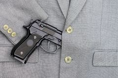 Business fight. Semi-automatic handgun in business suits Royalty Free Stock Images
