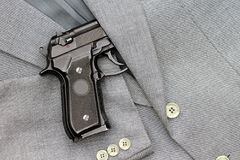 Business fight. Semi-automatic handgun in business suits Royalty Free Stock Photos