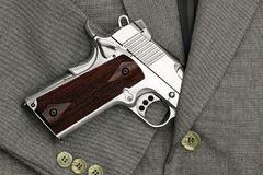 Business fight. Semi-automatic handgun in business suits, 45 pistol. royalty free stock image