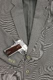 Business fight. Semi-automatic handgun in business suits Royalty Free Stock Image