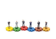 Business figures on colorful gears Royalty Free Stock Photos