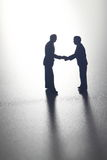Business figures shaking hands. Photograph of model business figures shaking hands backlit in black and white royalty free stock images