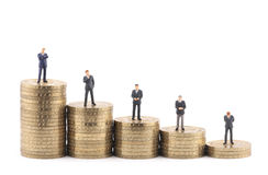 Business figures on stacks of coins. Tiny business figures on stacks of gold coins Stock Images