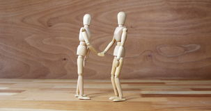 Business figurine shaking hands during meeting. Against wooden background stock footage