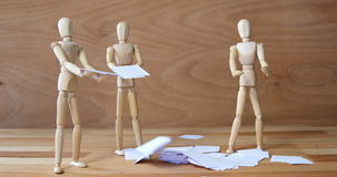 Business figurine standing near pile of documents falling from top. Against wooden background stock video footage