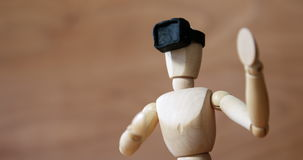 Business figurine using virtual headset reality. Against wooden background stock video