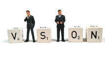 Business figurines forming the word vision. Two figurines forming the word vision royalty free stock image