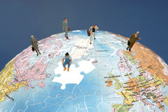 Business figurines on a globe Stock Photos
