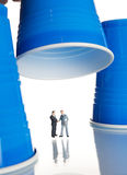 Business figurines under plastic coffee cups Royalty Free Stock Image