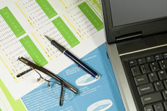 Business Finance. Laptop, pen anf glasses in finacial report royalty free stock image