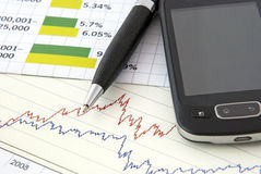 Business finance. Concept with chart, pen and cellular phone Stock Image